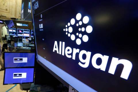 In a Monday, Nov. 23, 2015, file photo, the Allergan logo appears above a trading post on the f ...