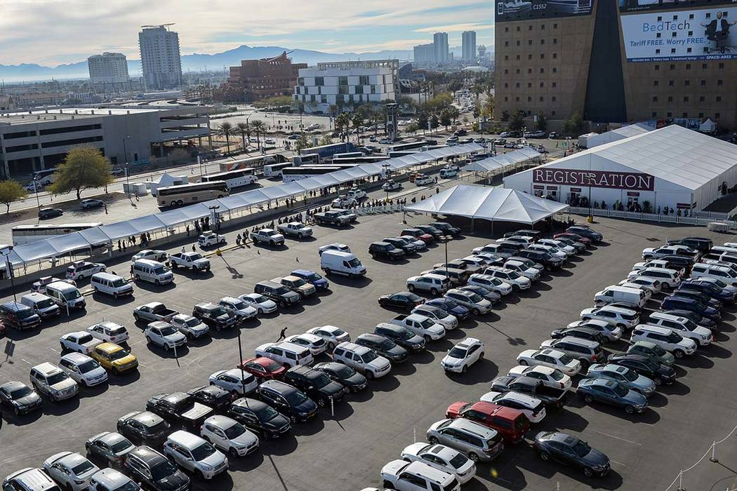 Rows of cars fill surrounding parking lots as crowds of people gather for the opening day of th ...
