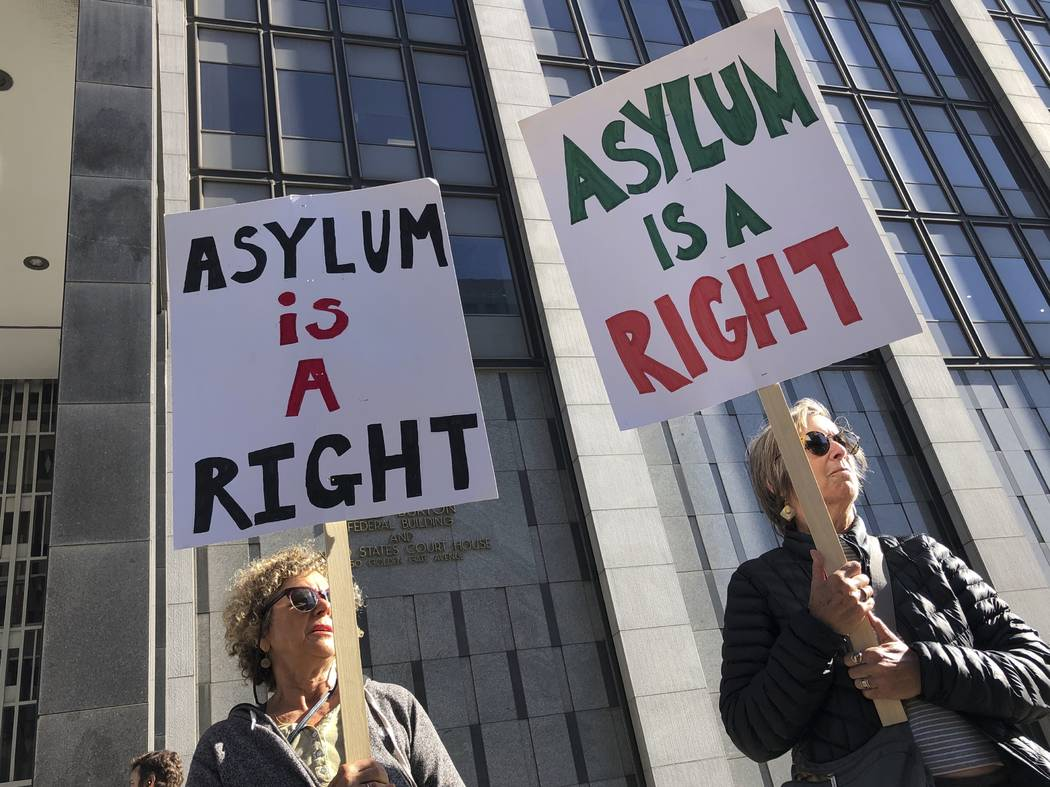 """Protestors hold signs that read """" Asylum is a Right"""" outside of the San Francisco Fed ..."""
