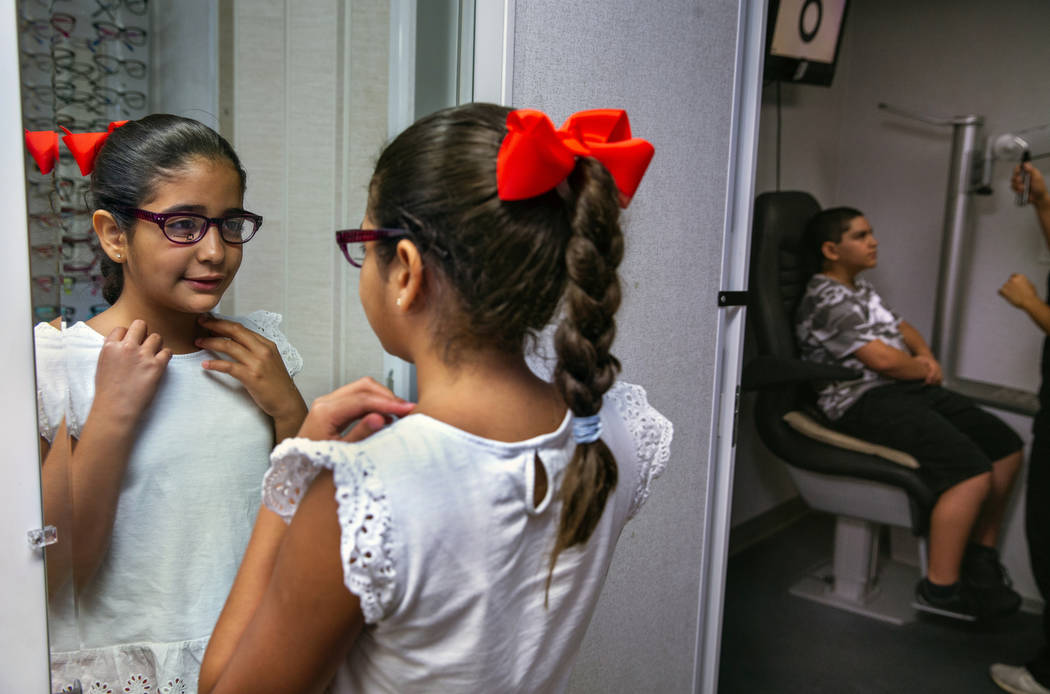 Esther Espinoza, 10, checks herself out in the mirror with wearing a new pair of glasses during ...