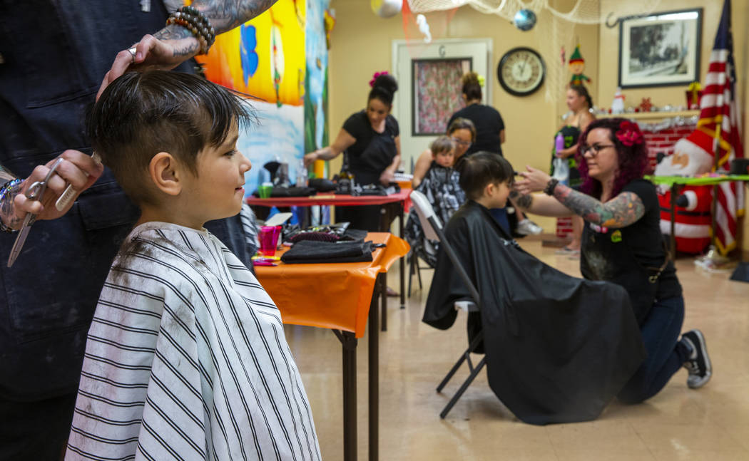 Toby Lewis, 5, from left, has his hair cut by stylist Ryan Glassford as Kaleb Lewis, 4, has his ...