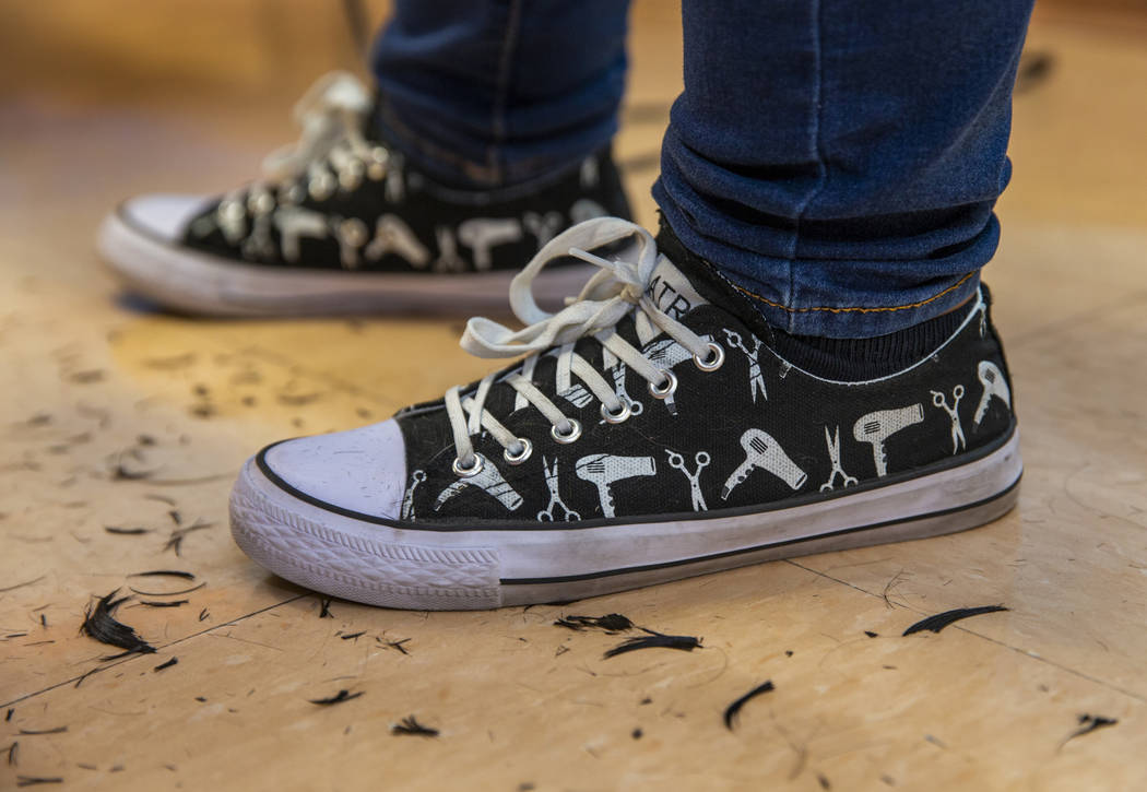 Hair stylist Sara Burton wears her custom sneakers while volunteering during a back-to-school e ...
