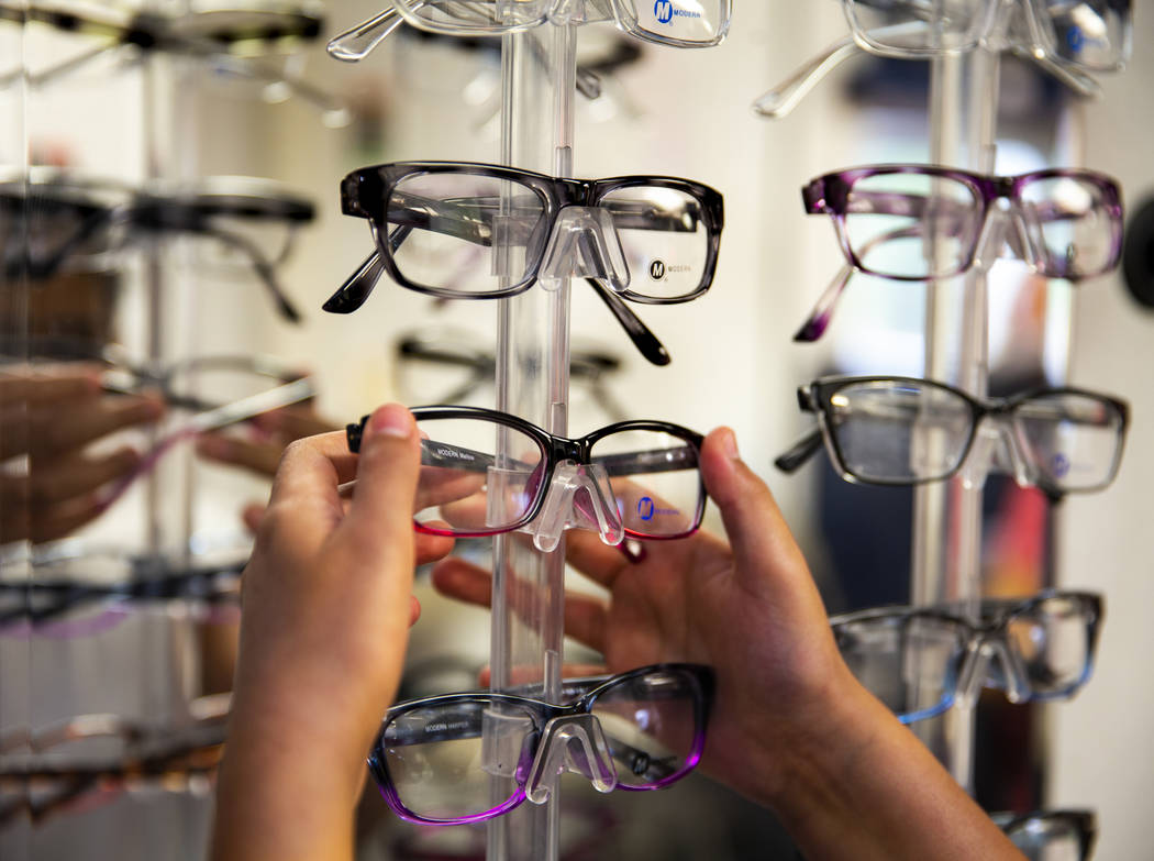 Esther Espinoza, 10, looks for a new pair of glasses during a back-to-school event at the Derfe ...