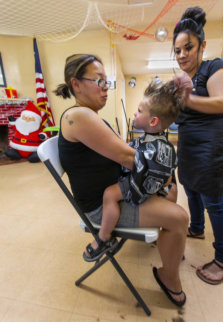 Soon Lewis, left, holds son Anderson, 2, as he receives his haircut from stylist Heather Delgad ...