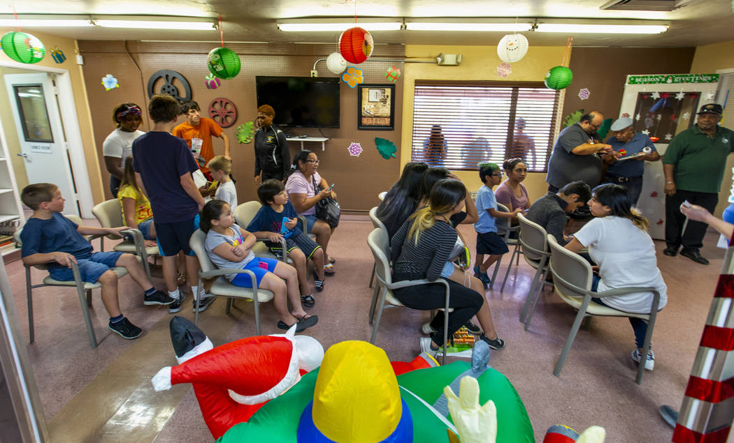 The haircut waiting area is full during a back-to-school event with free haircuts, eye exams an ...