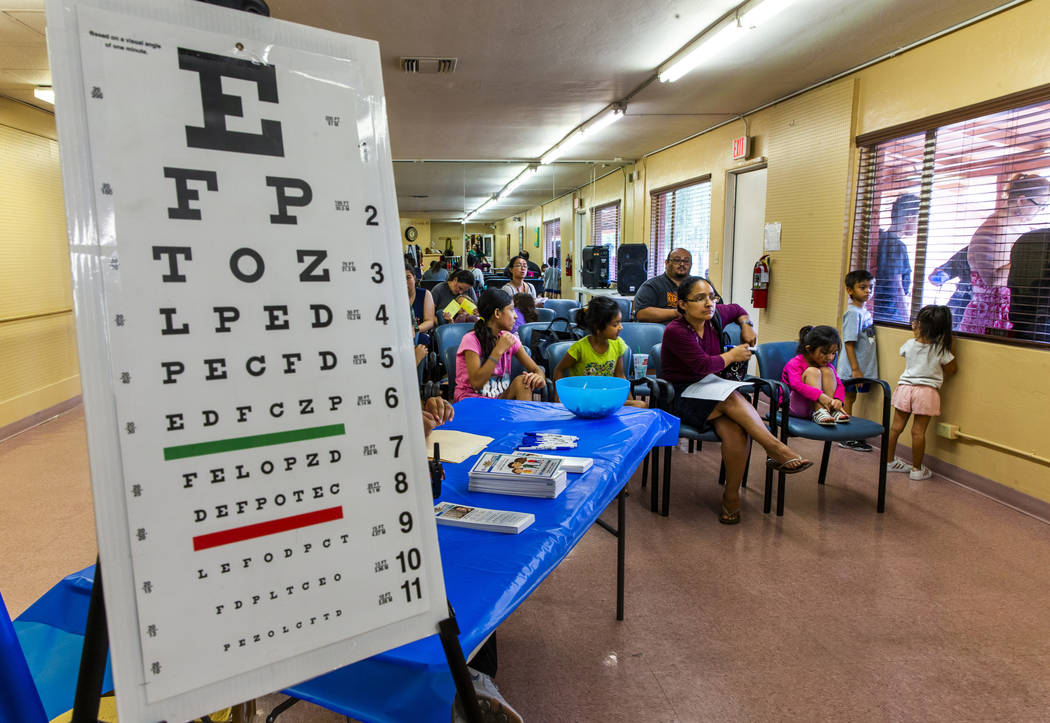 Students with parents await their turn for eye exams during a back-to-school event at the Derfe ...