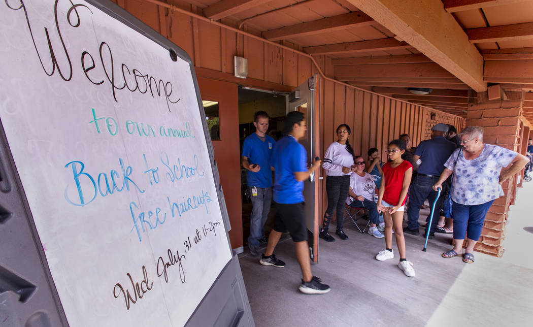 The line of people stays steady for a back-to-school event at the Derfelt Senior Center in Las ...