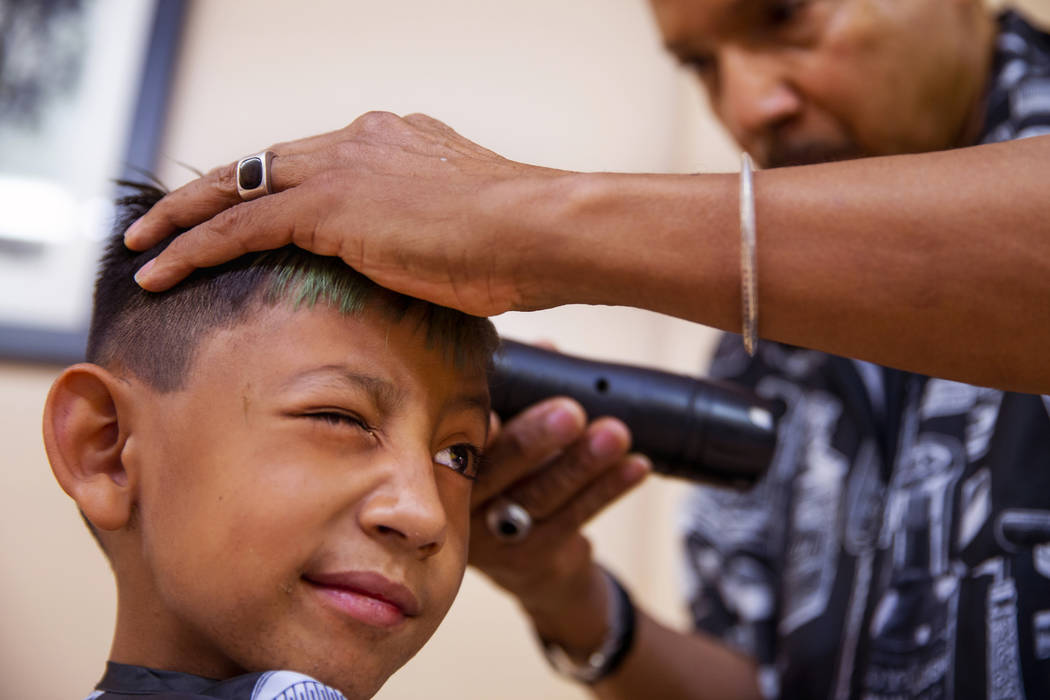 Victor Moreno, 5, squints his eye as hair stylist Thomas Rose trims him up during a back-to-sch ...