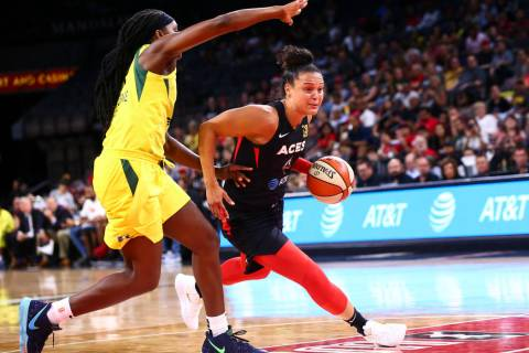 Las Vegas Aces' Kayla McBride drives to the basket past Seattle Storm's forward Crystal Langhor ...