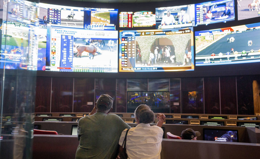 Bettors watch live sports at the CG Technology sportsbook at the Palms in Las Vegas, Thursday, ...