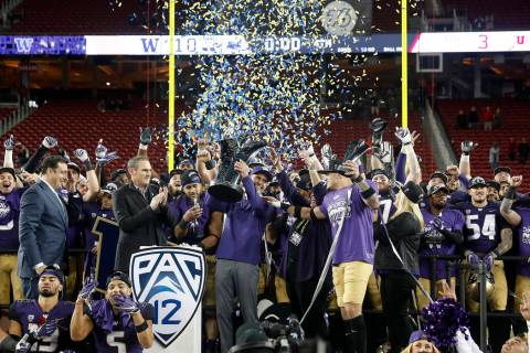 Washington coach Chris Petersen, center, raises the trophy as he celebrates with his players af ...