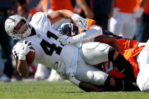 Oakland Raiders running back Keith Smith (41) is tackled by Denver Broncos linebacker Brandon M ...
