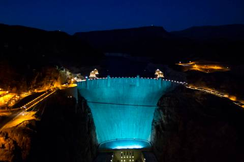 Hoover Dam, lit up turquoise to promote lung cancer awareness, as seen from O'Callaghan-Tillman ...