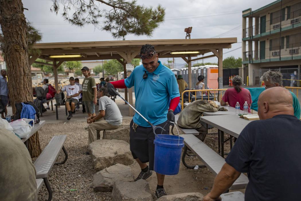 Harlan Thompson picks up trash at the Courtyard Homeless Resource Center in Las Vegas, Thursday ...