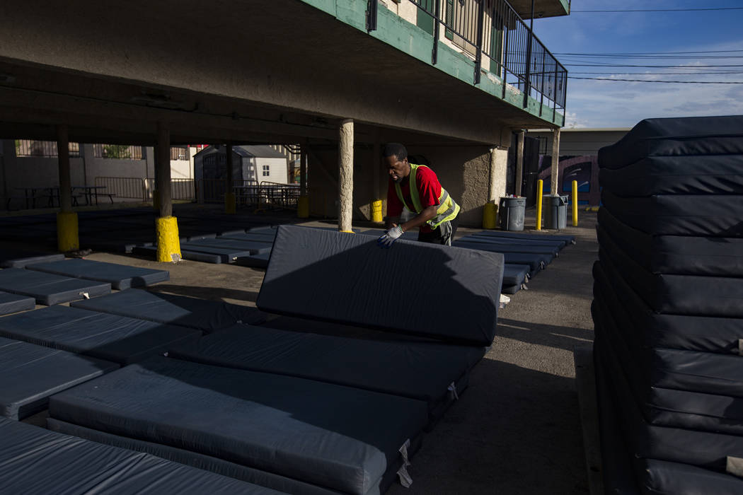 Chukwunedu Arah, a volunteer, places bed mats for clients at the Courtyard Homeless Resource Ce ...
