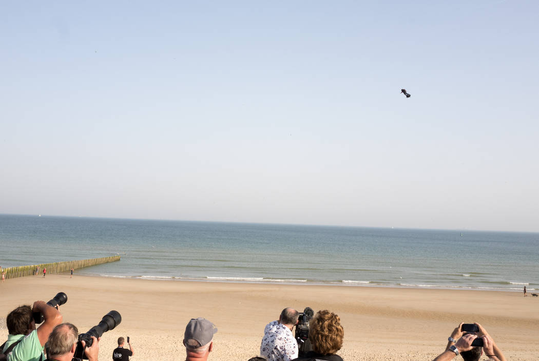People watch as Franky Zapata, a 40-year-old inventor, takes to the air in Sangatte, Northern F ...
