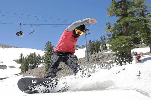 FILE - In this July 1, 2017 file photo, a snowboarder cuts throughout the snow at the Squaw Val ...