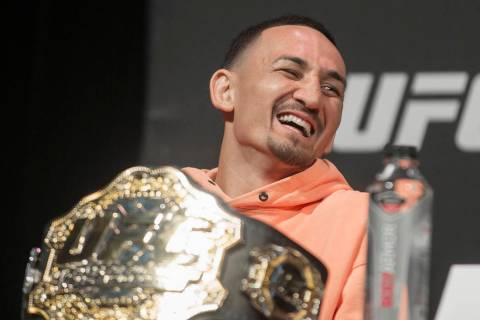 UFC featherweight champion Max Holloway shares a laugh with fellow fighters during a press conf ...