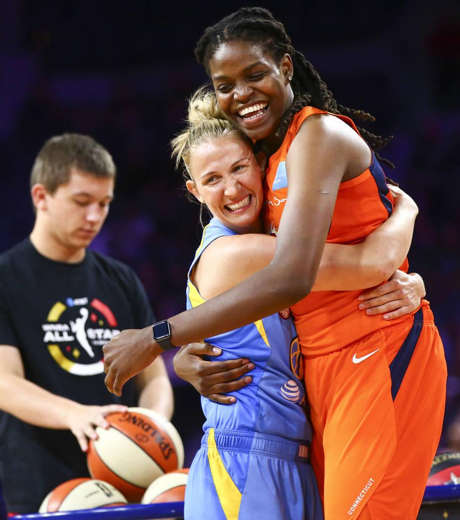 Chicago Sky's Courtney Vandersloot, left, hugs Connecticut Sun's Jonquel Jones during the WNBA ...