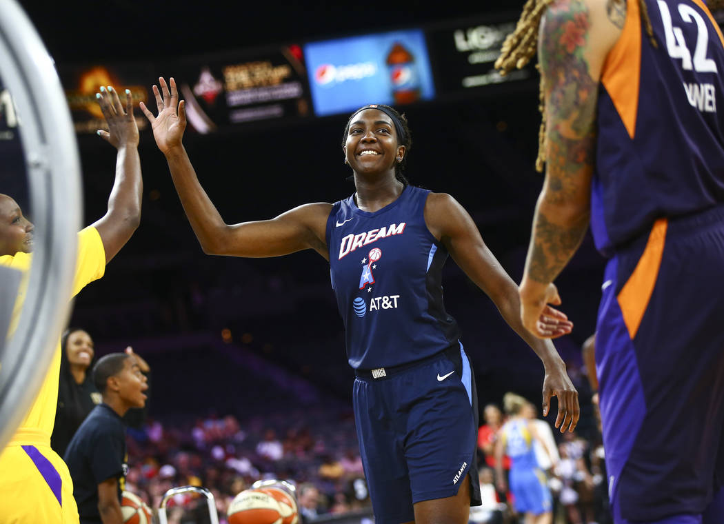 Atlanta Dream's Elizabeth Williams celebrates after competing in an obstacle course involving p ...