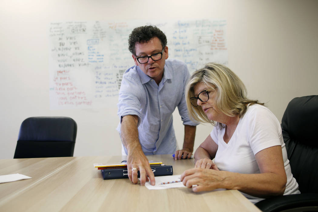 Instructor Lionel Huddlestone, left, and Donna Yoast participates in a French lesson at the All ...