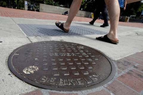 Pedestrians walk past a manhole cover for a sewer in Berkeley, Calif., Thursday, July 18, 2019. ...