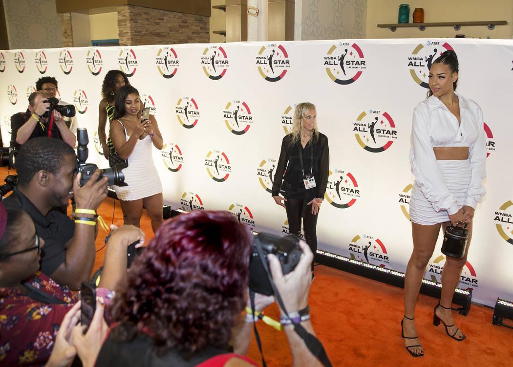 Las Vegas Aces center Liz Cambage, right, walks the WNBA Orange Carpet outside Della's Kitchen ...