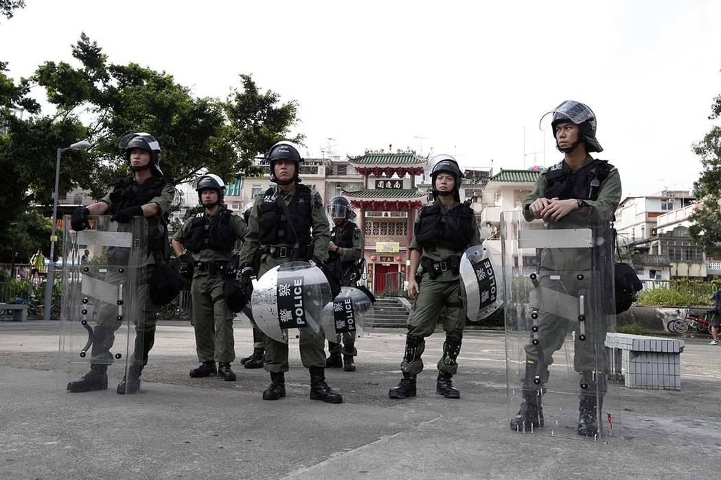 Riot police guard the entrance to a village at Yuen Long district in Hong Kong Saturday, July 2 ...