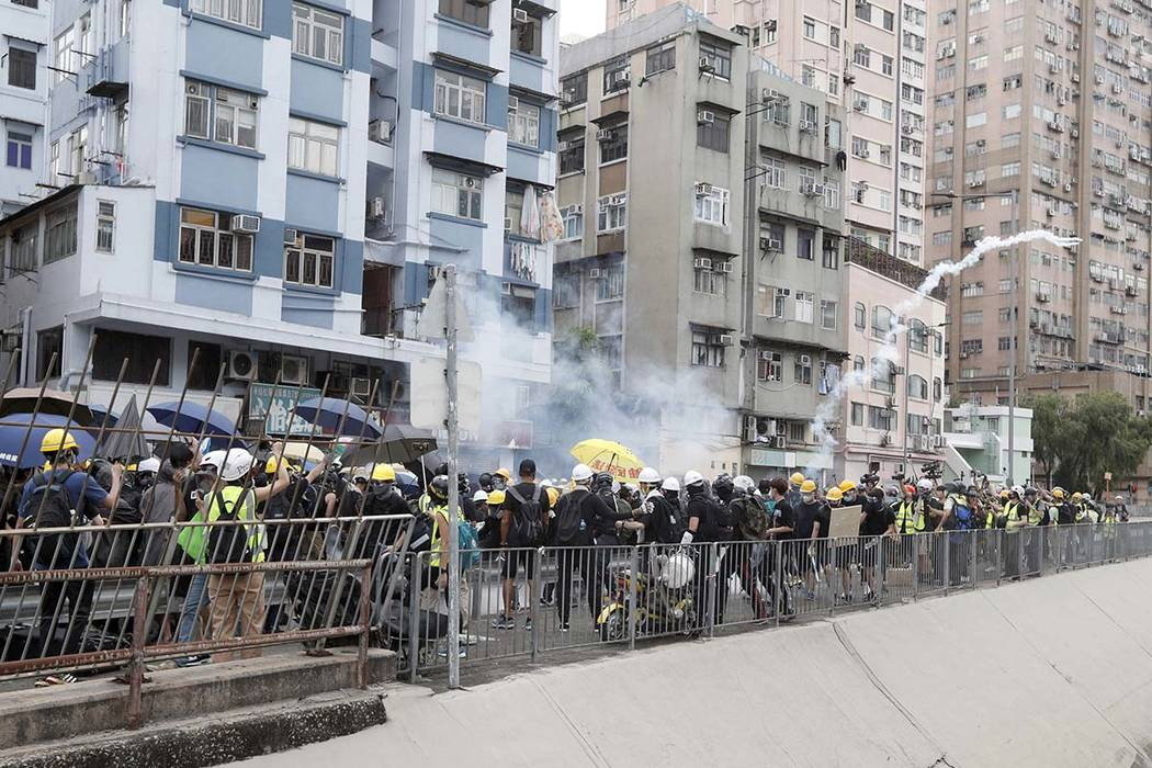 Protesters react to tear gas as they face off with riot police at the entrance to a village at ...