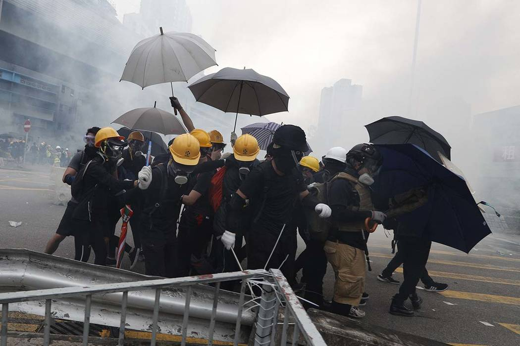Protesters react to tear gas during a face off with riot police at Yuen Long district in Hong K ...