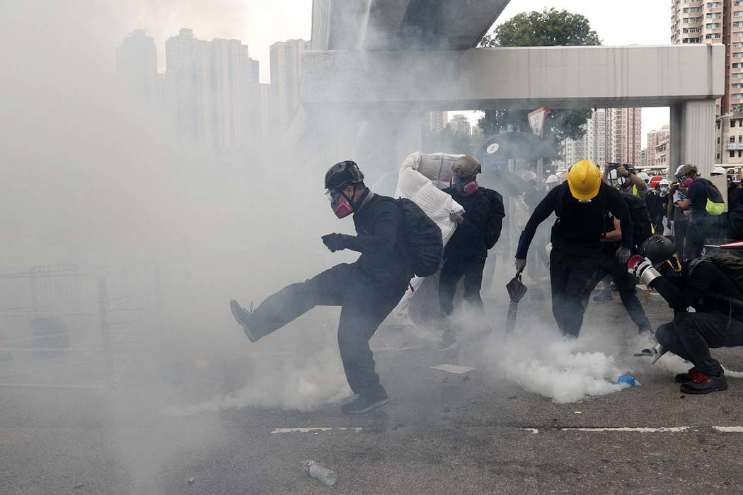 Protesters kick back and pick up tear gas canisters during a face off with riot police at Yuen ...