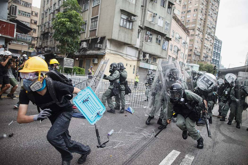 A protester flee from baton wielding police in Yuen Long district in Hong Kong on Saturday, Jul ...