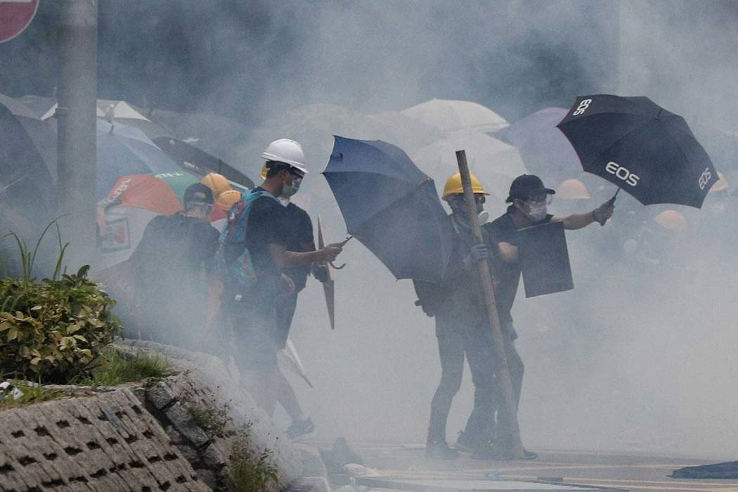 Protesters react to tear gas during a face off with riot police in Yuen Long district in Hong K ...