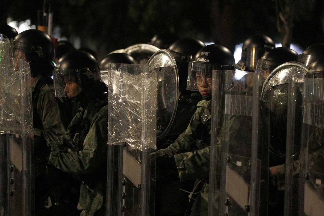 Riot police stand behind shields as they face off protesters in Yuen Long district in Hong Kong ...