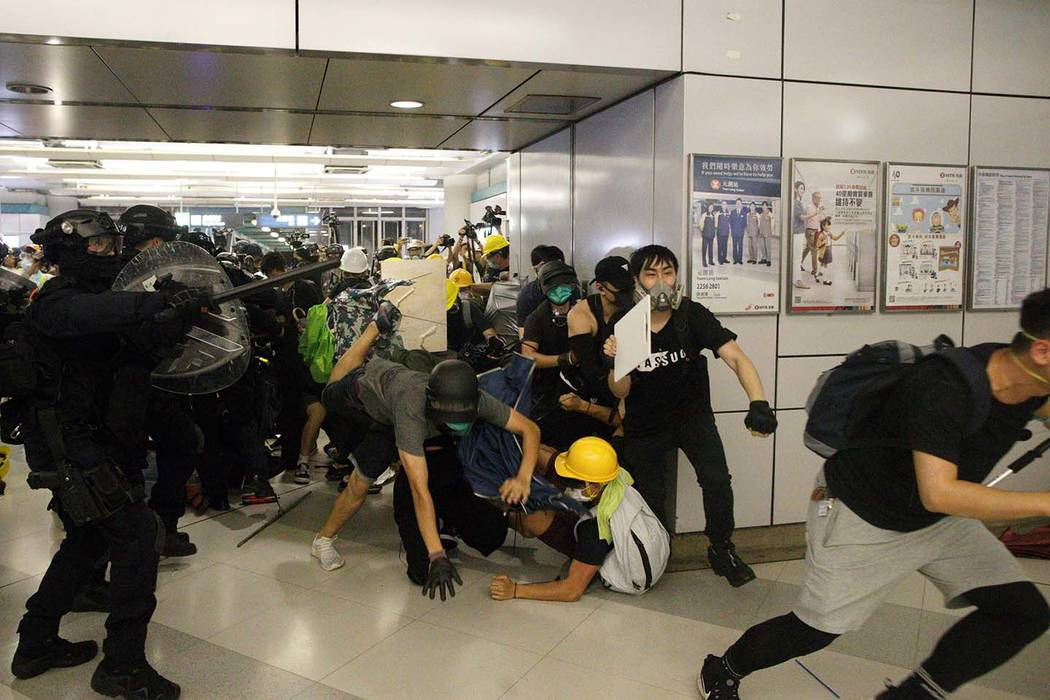 Special Tactical Squad officers attack protesters with batons who refused to disperse from a tr ...