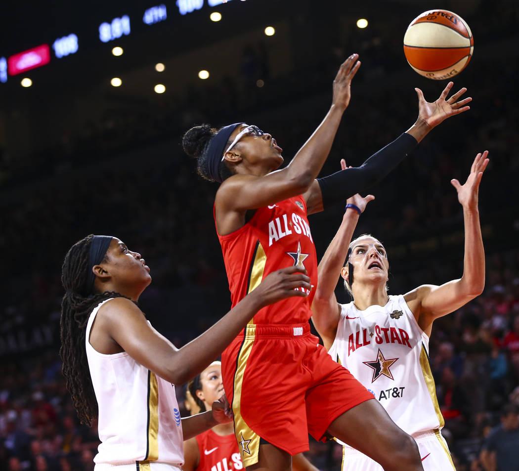 Chicago Sky's Diamond DeShields, center, goes to the basket between Connecticut Sun's Jonquel J ...