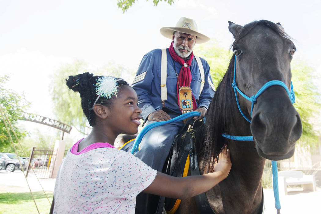 Tahji Moore, left, 9, pets the horse of Keith Hill, president trooper of the 9th and 10th Horse ...