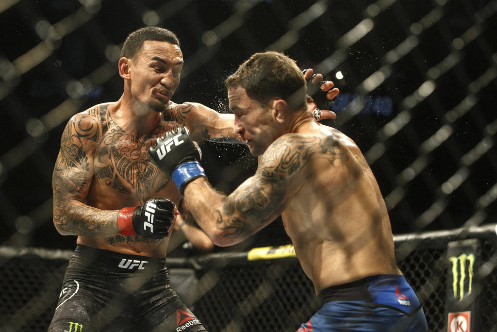 Max Holloway, left, fights Frankie Edgar during a mixed martial arts bout at UFC 240, in Edmont ...