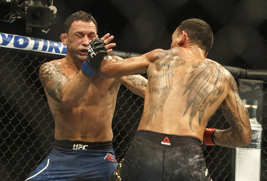 Max Holloway, right, punches Frankie Edgar during a mixed martial arts bout at UFC 240, in Edmo ...