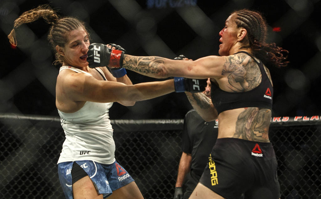 Cris Cyborg, right, hits Felicia Spencer during a mixed martial arts bout at UFC 240, in Edmont ...