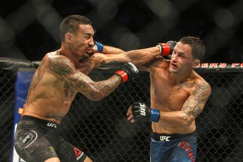 Max Holloway, left, and Frankie Edgar connect on each other during a mixed martial arts bout a ...