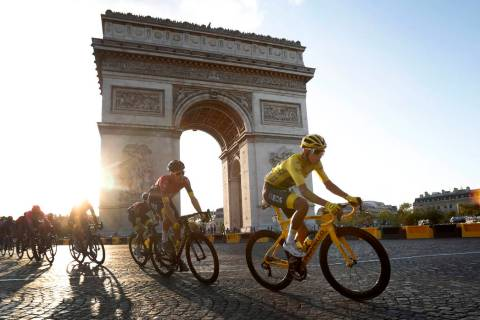 Colombia's Egan Bernal wearing the overall leader's yellow jersey, center, rides past the Arc d ...