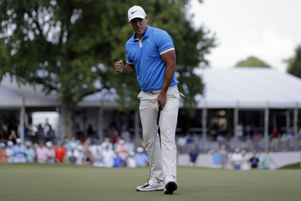 Brooks Koepka celebrates a birdie putt on the 17th green during the final round of the World Go ...