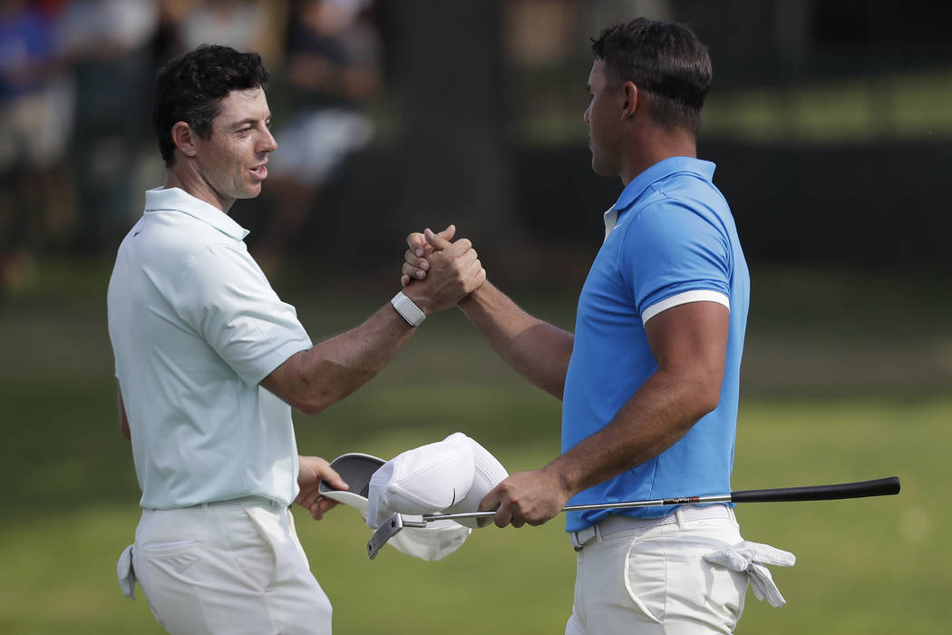Rory McIlroy, of Northern Ireland, left, shakes hands Brooks Koepka after Koepka won the final ...