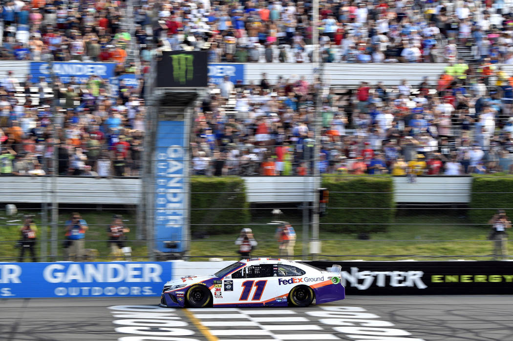 Denny Hamlin crosses the finish line to win a NASCAR Cup Series auto race, Sunday, July 28, 201 ...