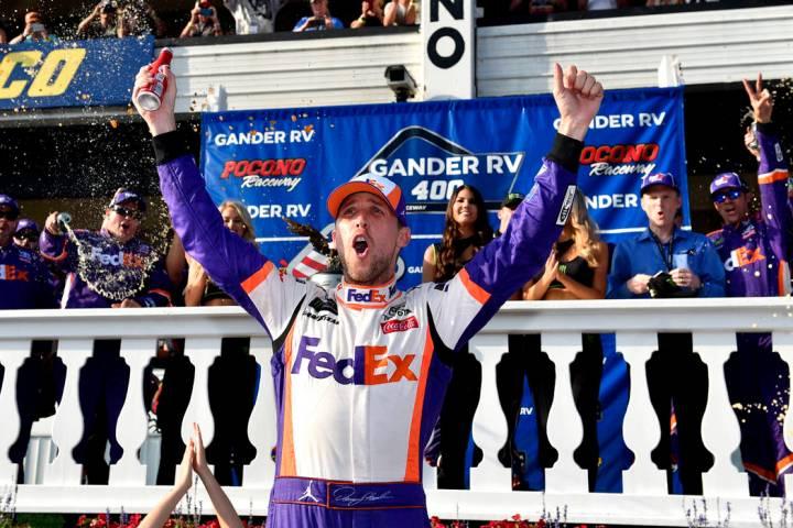 Denny Hamlin celebrates in Victory Lane after winning a NASCAR Cup Series auto race, Sunday, Ju ...