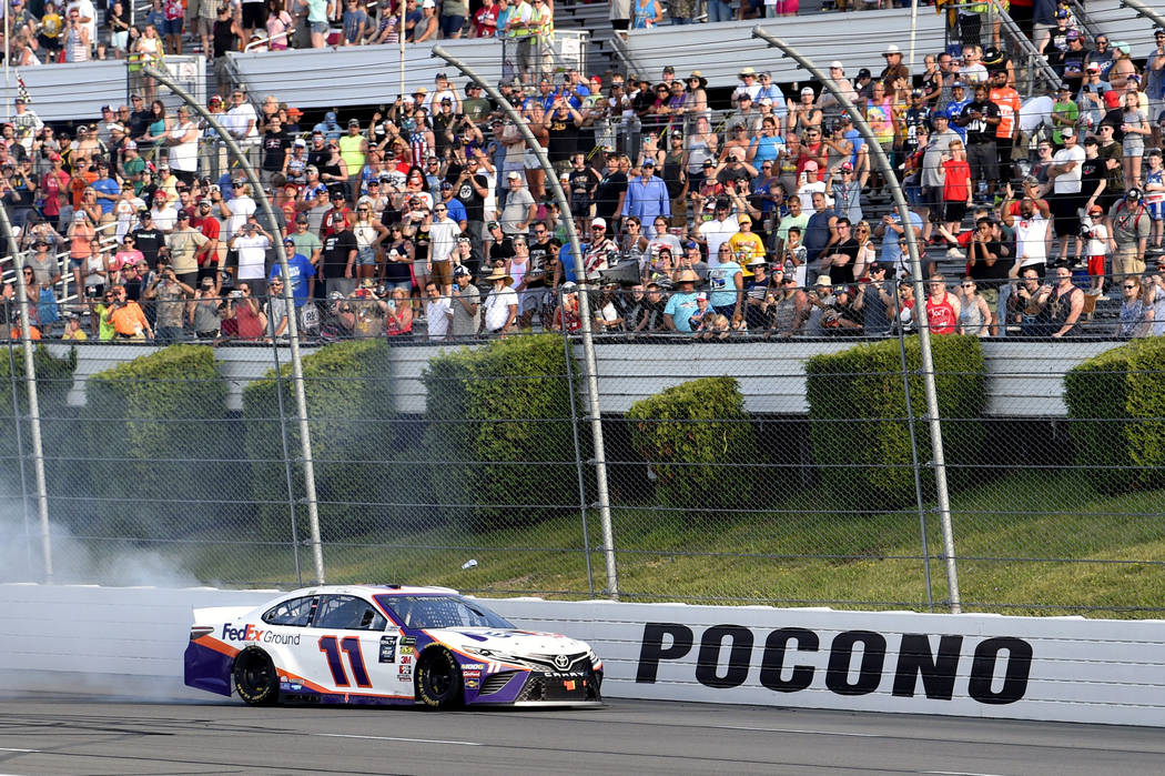 Denny Hamlin celebrates with a burnout after winning a NASCAR Cup Series auto race, Sunday, Jul ...