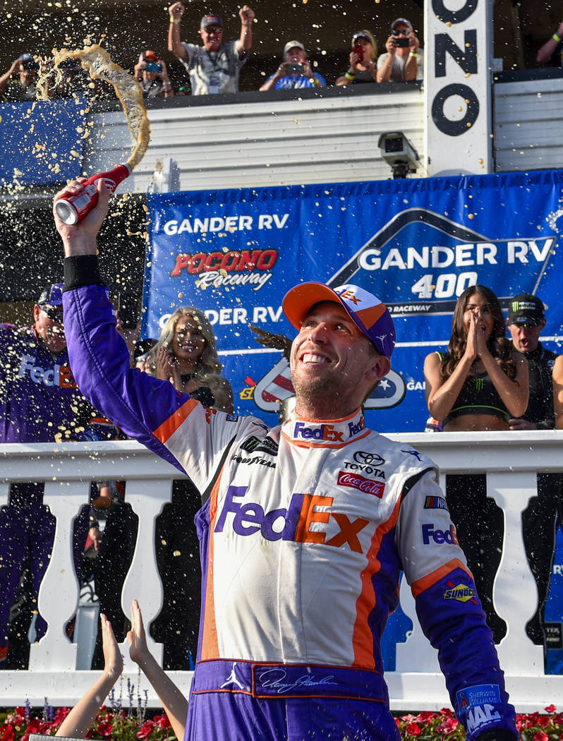 Denny Hamlin celebrates in Victory Lane after winning a NASCAR Cup Series auto race, Sunday, Ju ...
