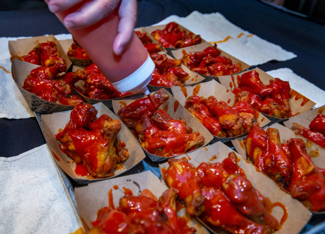 More sauce is poured on a new batch of wings as PT's Ranch hosts a $4,000 wing-eating challenge ...