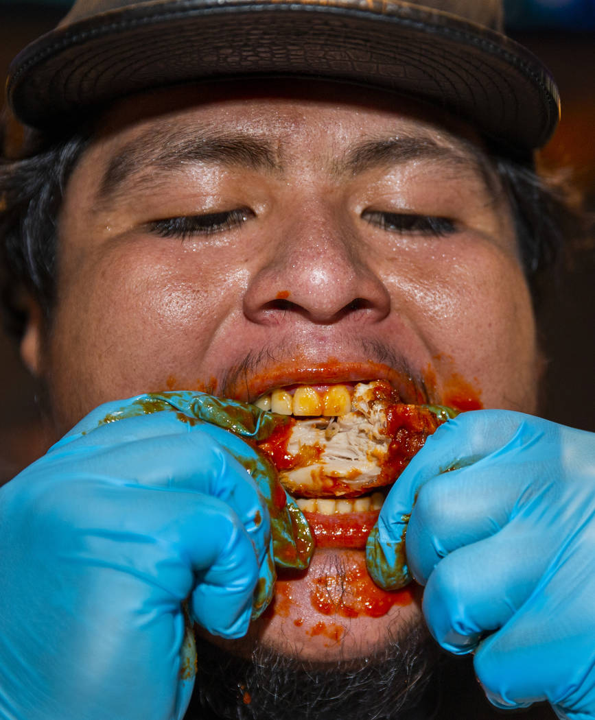 Competitor Alejandro Pascacio digs into a wing as PT's Ranch hosts a $4,000 wing-eating challen ...